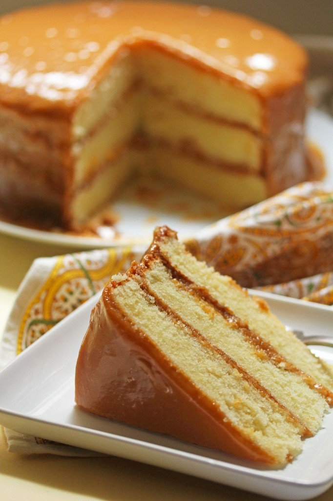 A slice of the 3-layer caramel cake on a white plate in the foreground with the caramel cake with a slice missing in the background.