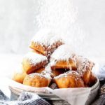 New Orleans beigents being sprinkled with confectioner's sugar against white background