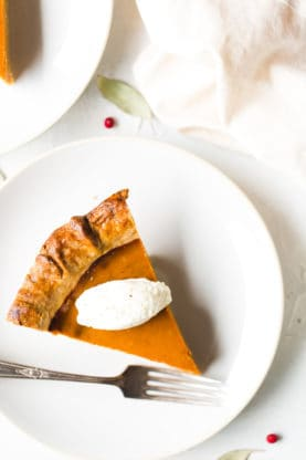 Close up shot of one slice of sweet potato pie with a dollop of whip cream on top sitting on a white plate with a silver fork next to it.