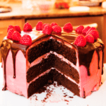 Raspberry chocolate cake topped with fresh raspberries and chocolate sauce drizzling down the sides with a slice missing