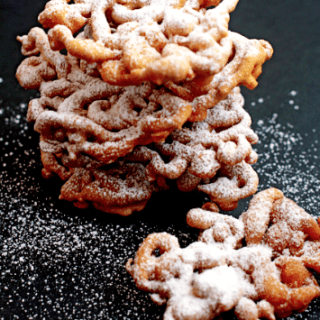 A stack of funnel cakes with powdered sugar on top