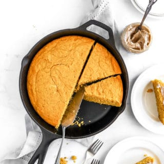A cast iron skillet filled with pumpkin cornbread that is sliced and on white plates with cinnamon butter