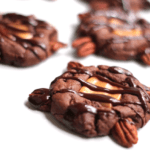 A turtle cookie drizzled with chocolate sauce on top with more cookies in the background