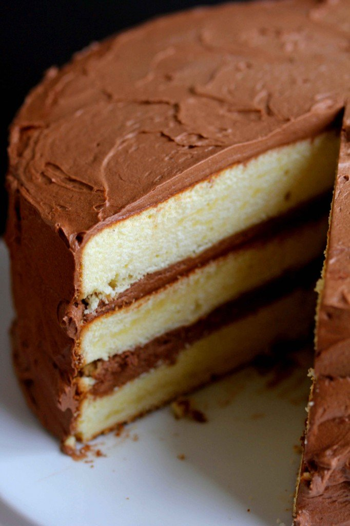 Yellow cake with chocolate frosting with a slice missing.