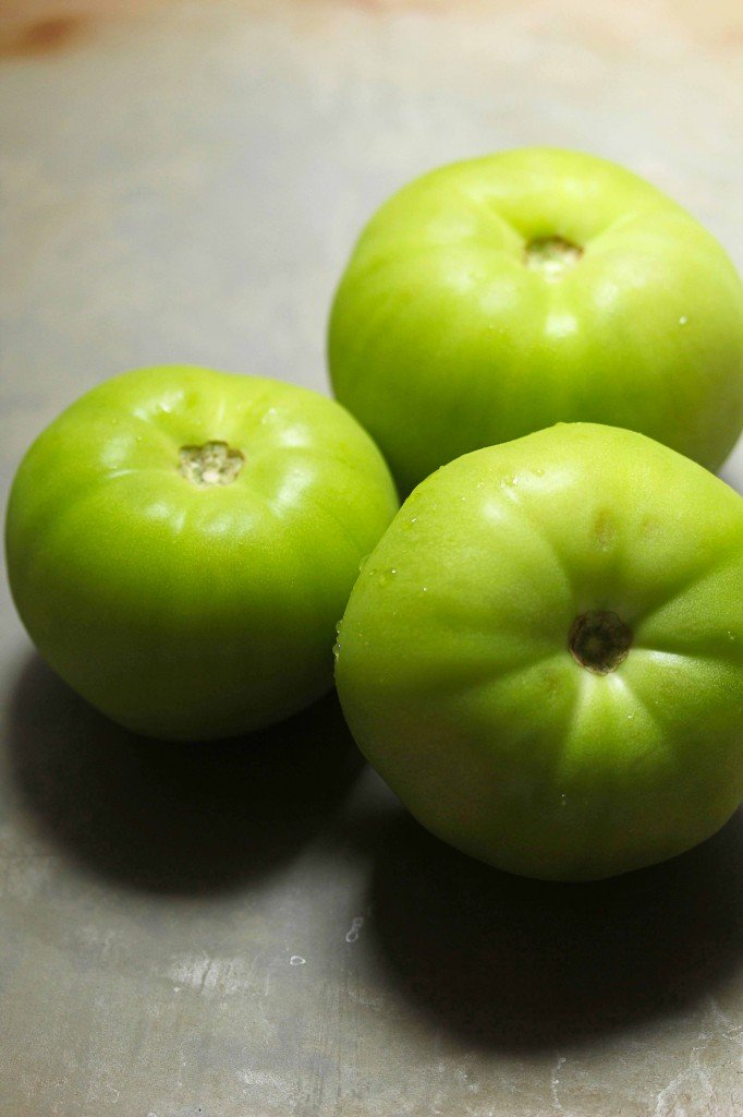 Three green tomatoes that would be perfect for this fried green tomato recipe.
