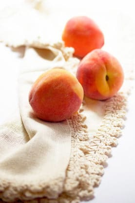 Fresh summer ripe peaches against white background ready to make pie