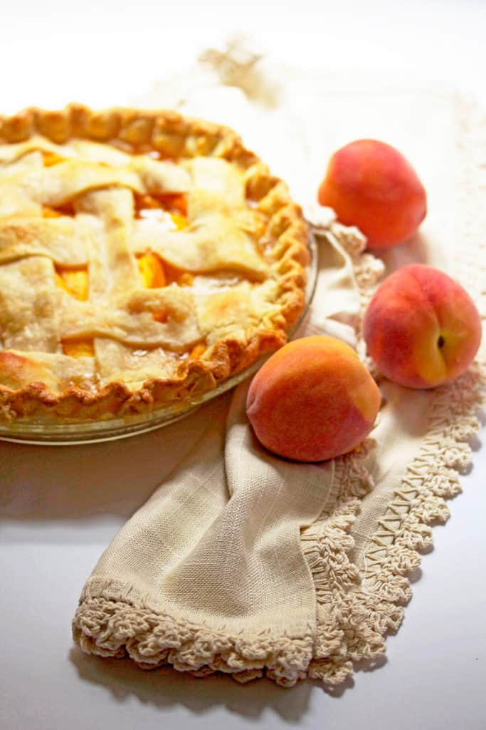 A peach pie with lattice crust on a white background with scattered fresh peaches against beige napkin.