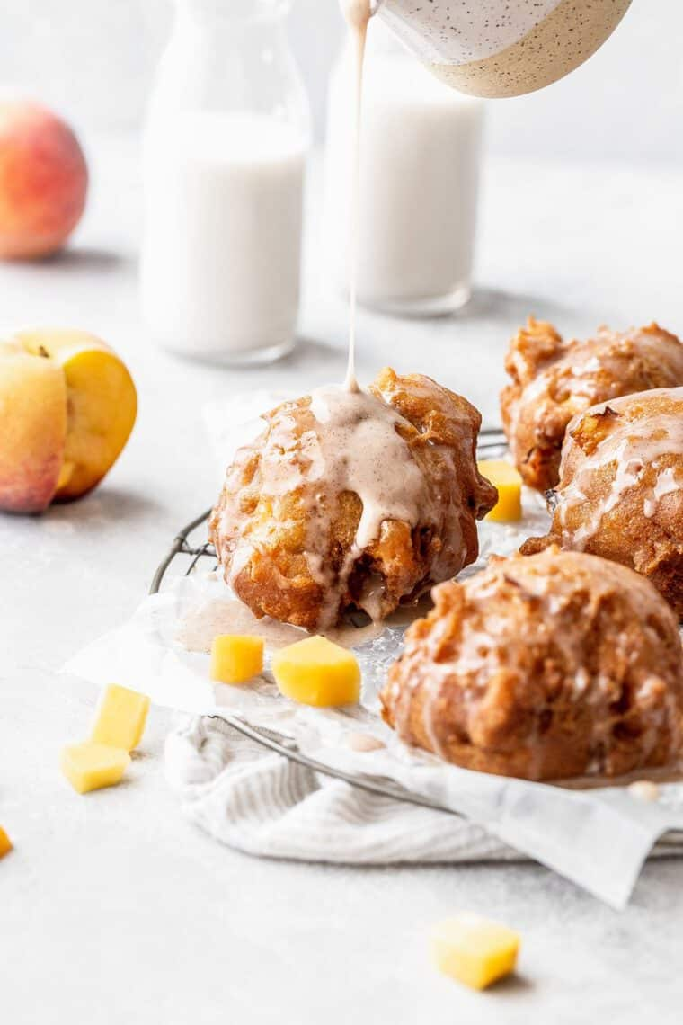 Delicious peach fritters against white background with icing