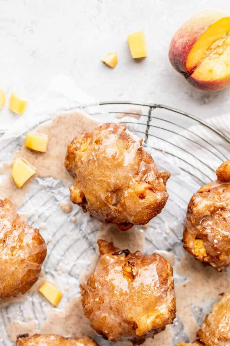 Overhead of fried peach fritters with icing against white background