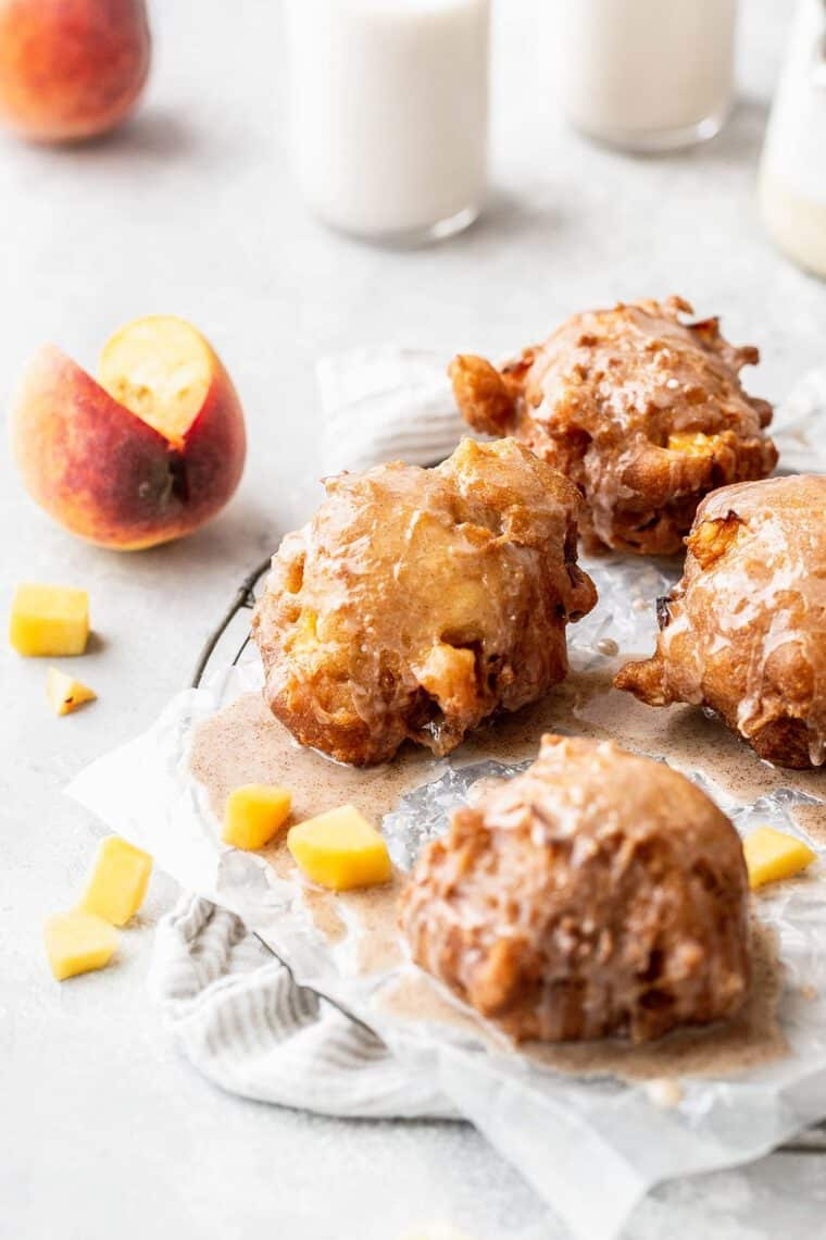 Fried fritters with peaches against white background
