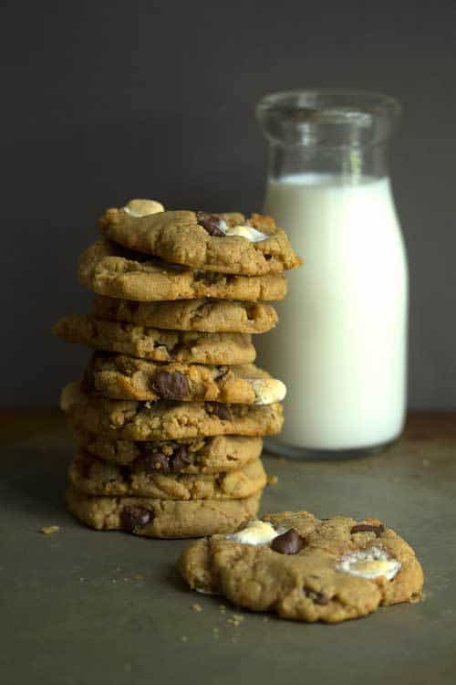 Several Jif S'more Peanut Butter Cookies stacked on top of each other with a glass of milk in the background.