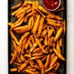 A large baking pan filled with sweet potato fries and a serving dish of ketchup