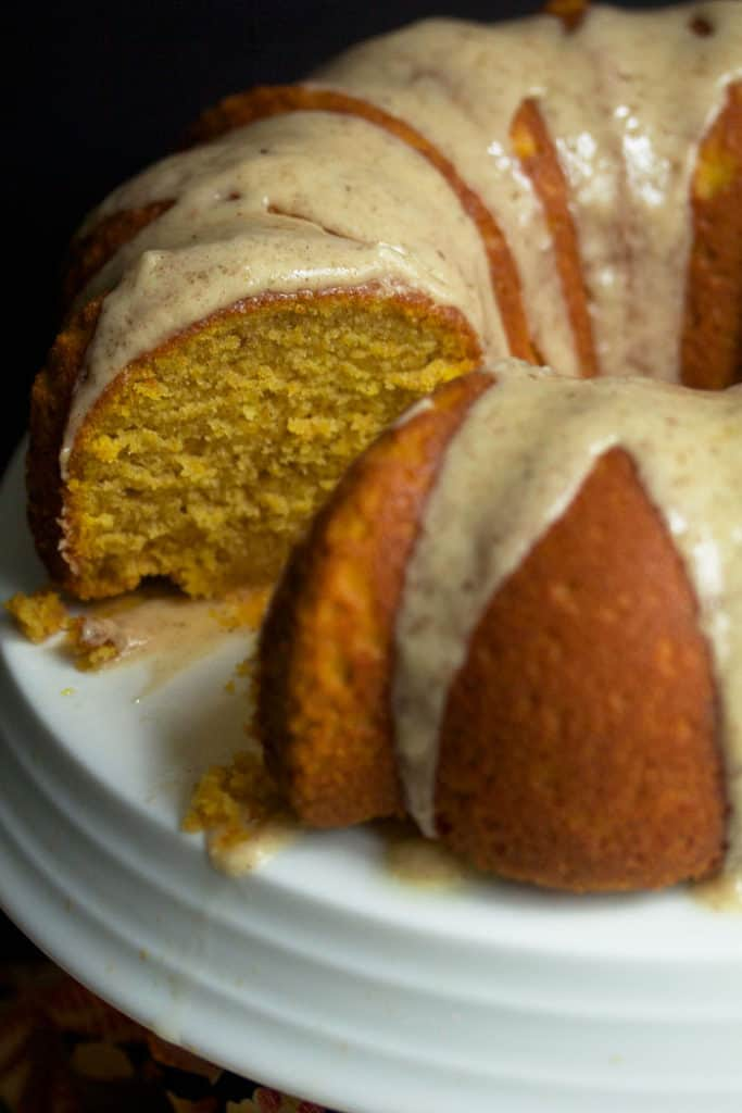 Close up of a Pumpkin Pound Cake with brown butter glaze on top with one slice cut out.