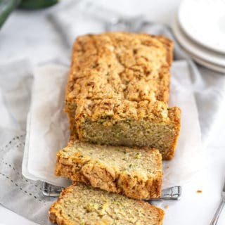 Zucchini bread loaf on white parchment paper with three slices leaning on each other