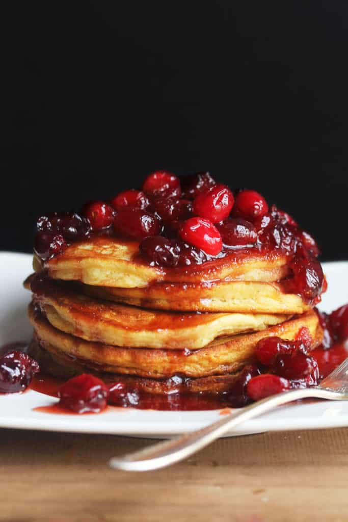 Eggnog Pancakes sitting on a white plate topped with Cranberry Maple Syrup