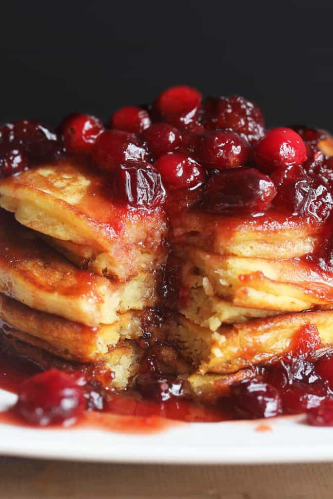Eggnog Pancakes sitting on a white plate topped with Cranberry Maple Syrup with a slice of the pancake stack missing.