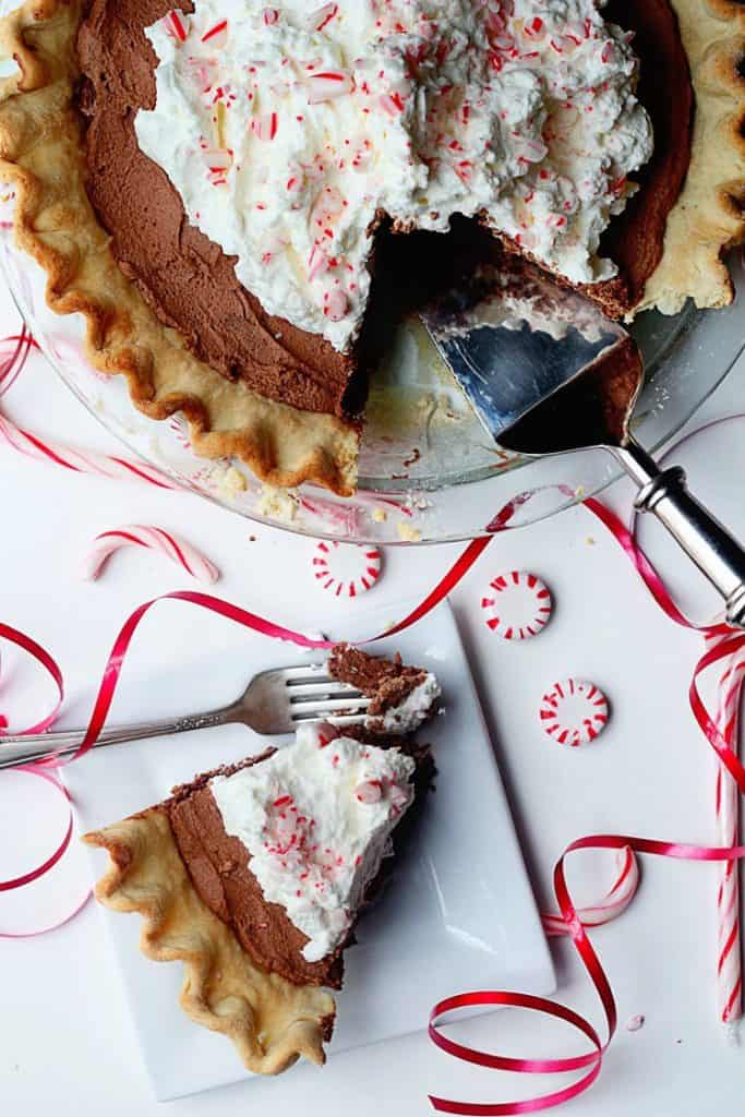 French Silk Pie topped with peppermint. One slice has been cut out of the pie.