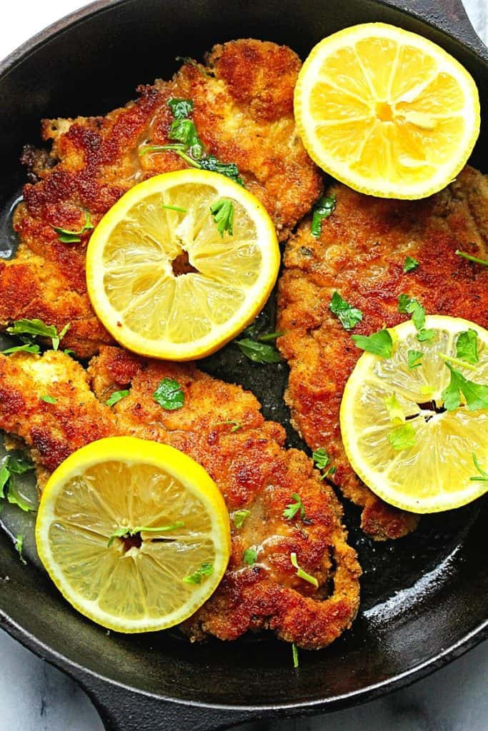 Delicious bread crumb crusted chicken paired with a classic lemon wine sauce. One of the best breaded chicken and chicken breast recipes on the internet!