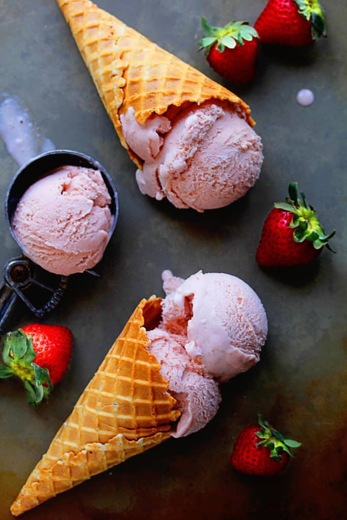 Homemade Strawberry Ice Cream contained in an ice cream scooper and waffle cones.