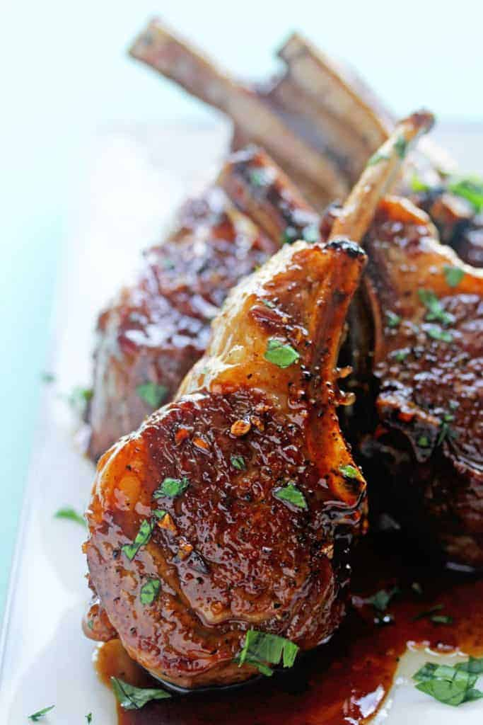 Learn how to cook lamb chops with this close up of the best lamb chop recipe pictured here resting on a white plate.