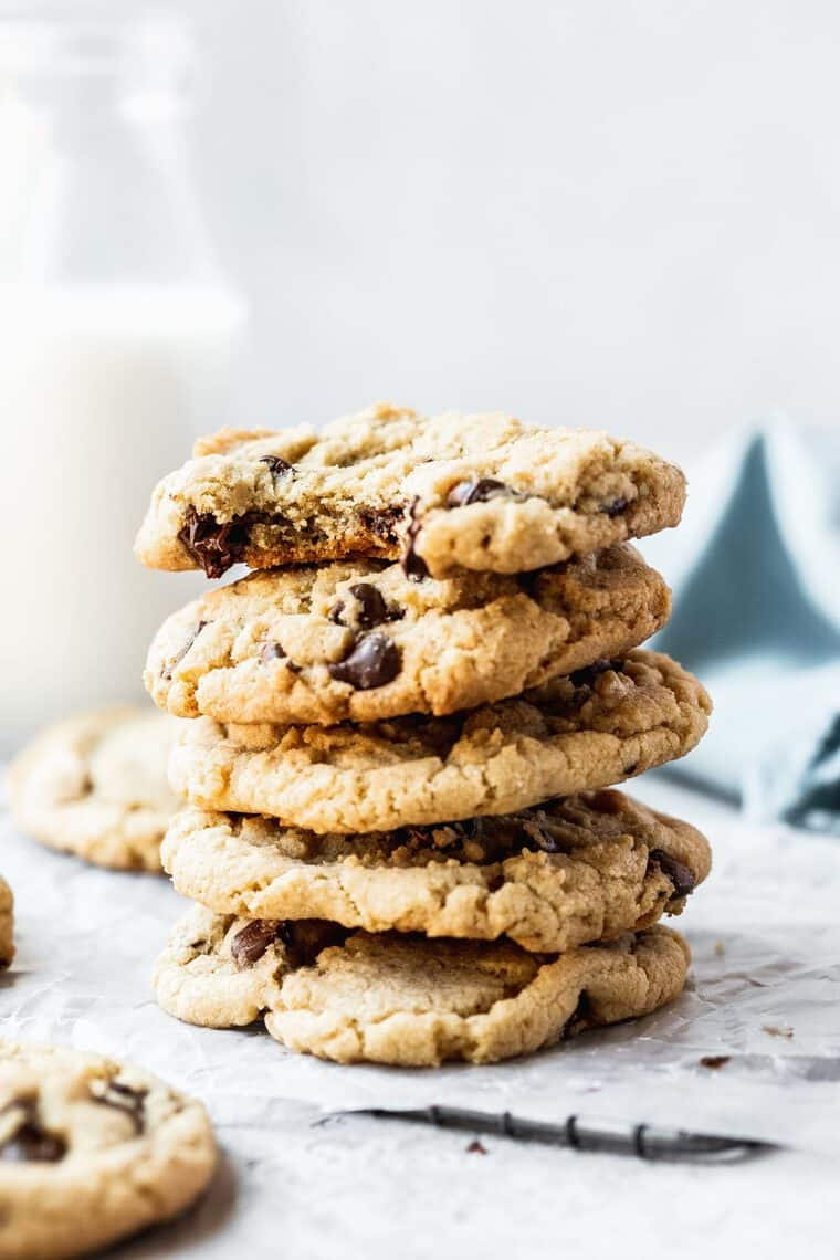 A stack of chewy chocolate chip cookies against white background with pitcher of milk