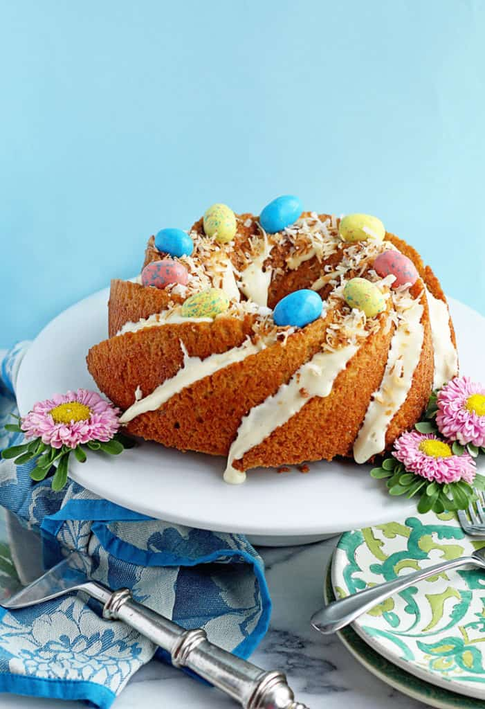 Easy Carrot Cake Recipe displayed on a white cake plate topped with Easter egg candies and coconut.