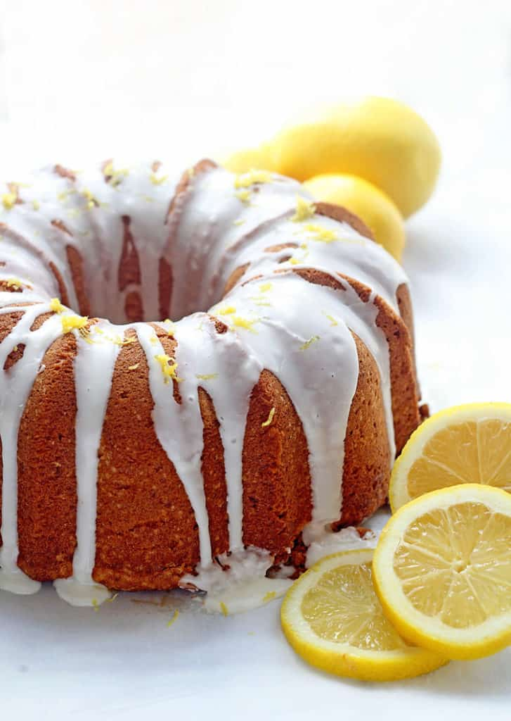 Lemon Pound Cake (Ultimate Lemon Cake Recipe) topped with a lemon drizzle surrounded by lemon slices.