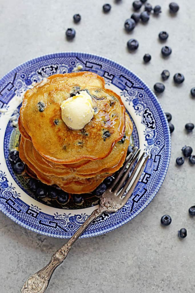 Overhead shot of this Blueberry Pancake Recipe topped with syrup and butter and surrounded by fresh blueberries.