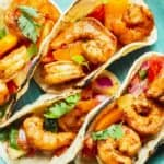 A close up of four shrimp tacos with salsa on a blue plate ready to serve