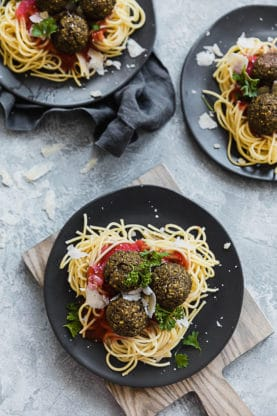 Three bowls of lentil meatballs sitting on a bed of spaghetti and marinara sauce.