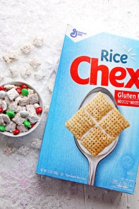 Eggnog Muddy Buddies in a bowl next to a box of Rice Chex cereal.