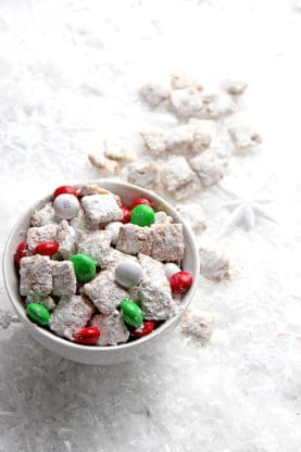 Eggnog Muddy Buddies in a white bowl with holiday M&M candies.
