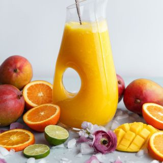 Mango fruit punch in a vessel surrounded by gorgeous fresh fruits