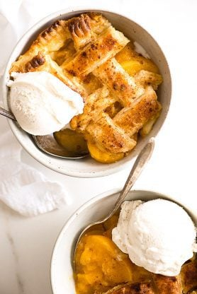 Two individual servings of homemade peach cobbler contained in small white bowls and topped with vanilla ice cream.
