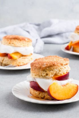 Brown Sugar Peach Shortcake Recipe- Buttery flaky shortcake biscuits get topped with brown sugar soaked ripe peaches and fluffy whipped cream for the ultimate summer delight. #peach #peaches #shortcake #biscuits