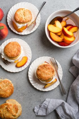 Learn how to make shortcakes with this brown sugar shortcake recipe sitting on white plates surrounded by biscuits and peaches.