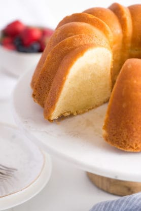 Sour Cream Pound Cake Recipe sitting on a white cake plate with a white bowl of fresh berries in the background.