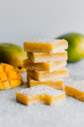 Lemon Bar Recipe with mango in the background.