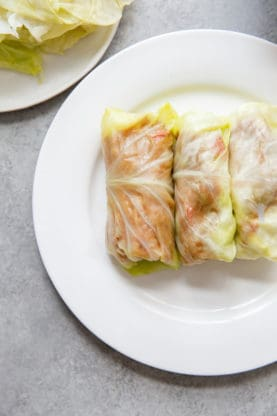 Three uncooked stuffed cabbage rolls sitting on a white plate.