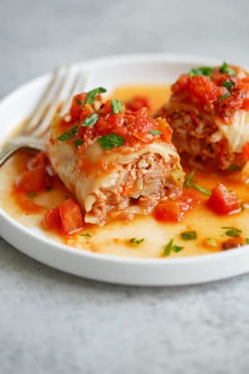 Stuffed Cabbage Rolls Recipe– Cabbage leaves are stuffed with rice and ground beef and complimented with a tangy flavorful tomato sauce seasoned with herbs and spices. Each bite is pure comfort, and you'll find yourself wanting to make these not only for easy weeknight dinners but for holiday gatherings.