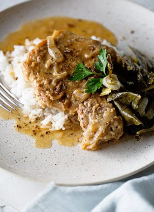 Southern Smothered Pork Chops Recipe - Lightly breaded pork chops are smothered in a rich savory and well seasoned brown gravy resulting in the perfect Southern classic.