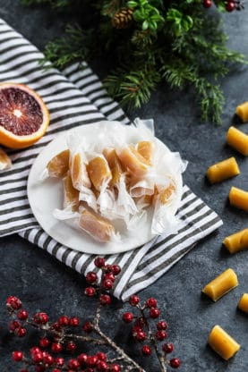 Wrapped Blood Orange Caramels on white plate with black and white striped napkin with blood oranges