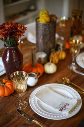 Wood table with dinner rolls and sweet potatoes over tablescape