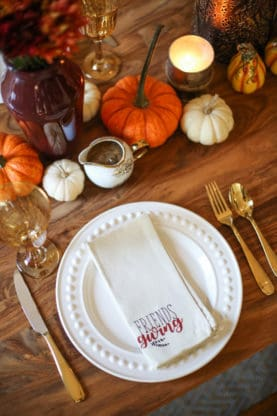 Friendsgiving white napkin overhead on wood table