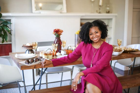Jocelyn Delk Adams sitting next to Friendsgiving tablescape