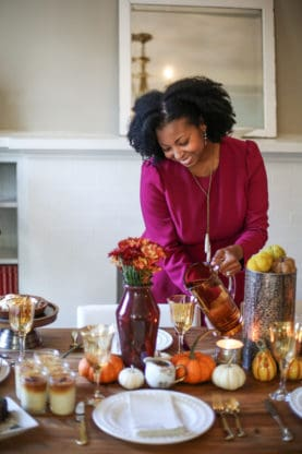 Jocelyn Delk Adams pouring from orange pitcher over Friendsgiving tablescape
