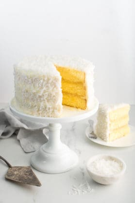 Sliced Pineapple Coconut Layer Cake on white cake stand with slice of cake on white plate with white background