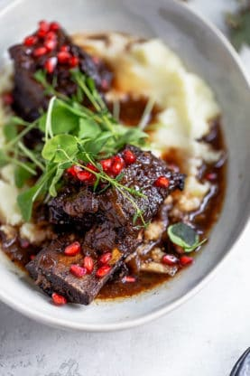 Pomegranate glazed short ribs over mashed potatoes with pomegranate seeds and green garnish in white bowl