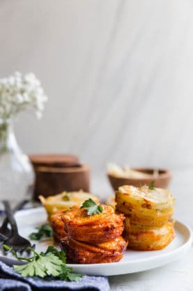 Sweet Potato Stacks and Yukon Gold Potato Stacks on white plate with parsley garnish and white flowers background
