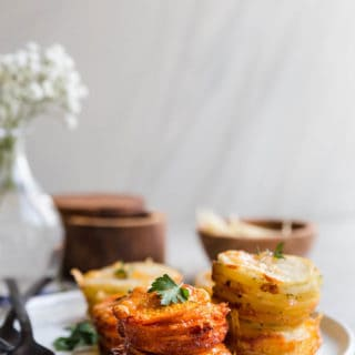 Sweet Potato Stacks and Yukon Gold Potato Stacks on white plate with parsley garnish and white flowers background